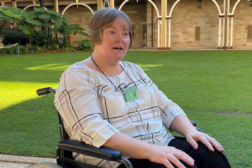 Patricia Clayton en su silla de ruedas en el suelo verde del Parlamento.